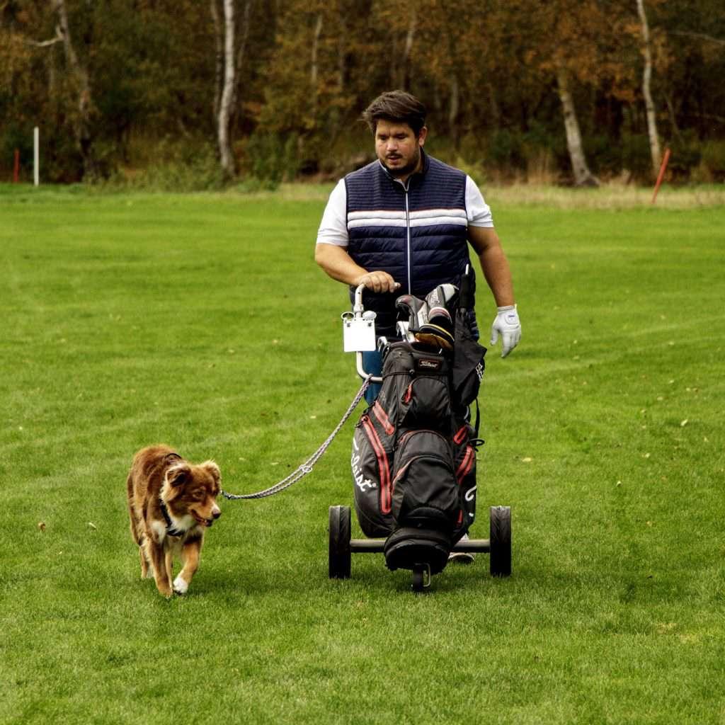 Golfer mit Hund an der Leine auf der Runde
